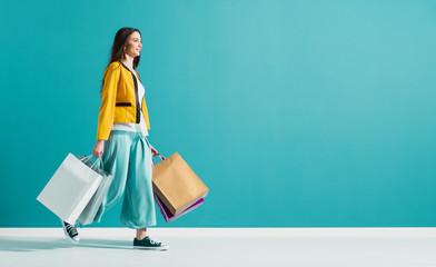 Uśmiechnięta kobieta spaceru i gospodarstwa torby na zakupy