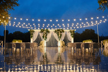 Night Wedding Ceremony With Arch, Orchid Flowers, Chairs And Bulb Lights In Forest Outdoors, Copy Space. Wedding Decorations