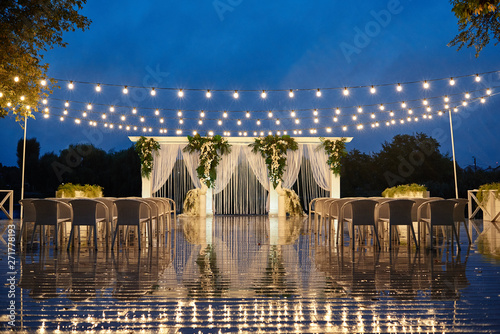 Foto Night wedding ceremony with arch, orchid flowers, chairs and bulb lights in forest outdoors, copy space