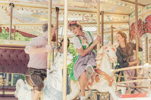 Fotografie, Obraz  Gruppe von Freunden fährt mit dem Karussell auf dem Jahrmarkt Vergnügungspark
