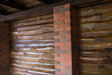 Decorative wall of pine boards painted with varnish. Wood texture. Brick column.