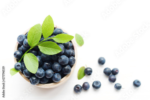Fotografija Fresh bilberry in a wooden bowl on a white background, top view