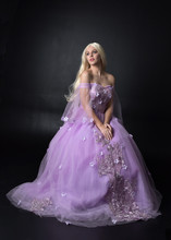 Full Length Portrait Of A Blonde Girl Wearing A Fantasy Fairy Inspired Costume,  Long Purple Ball Gown With Fairy Wings,   Sitting Pose  On A Dark Studio Background.