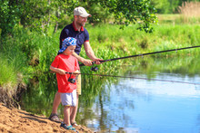 Family On Fishing. Father And Son With Fishing Rod Catching Fish In River