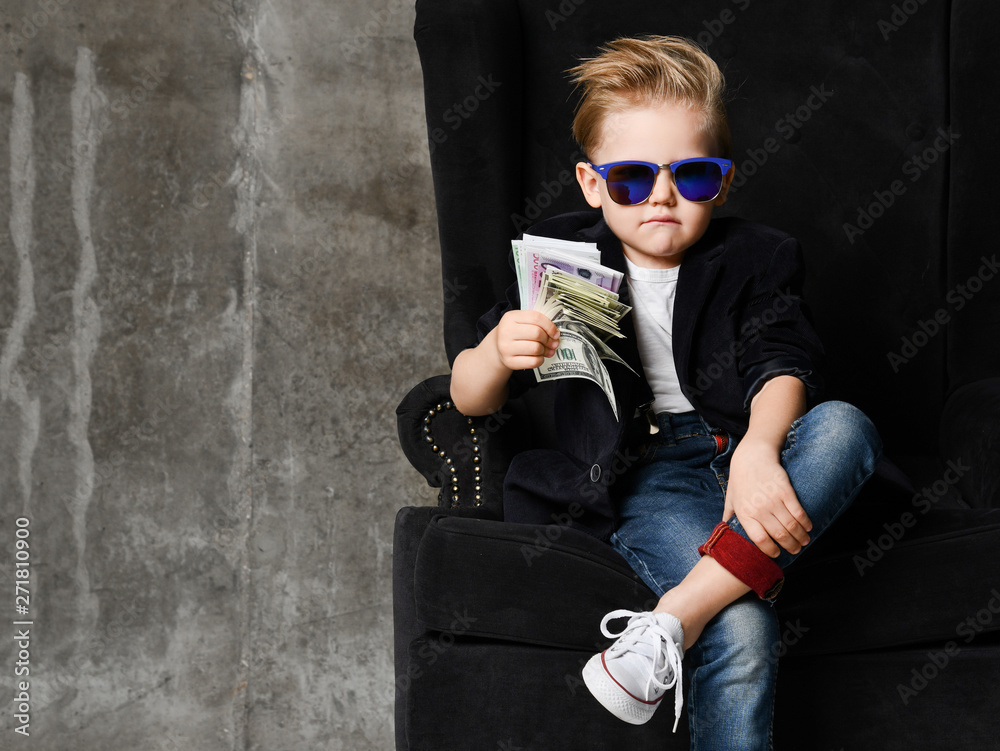 Leinwandbild Motiv - Dmitry Lobanov : Portrait of self-confident rich kid boy siting in luxury armchair with bundles of dollars cash in his hand at text space