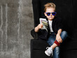 Leinwandbild Motiv Portrait of self-confident rich kid boy siting in luxury armchair with bundles of dollars cash in his hand at text space