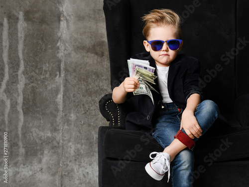 Foto auf Leinwand Akt Portrait of self-confident rich kid boy siting in luxury armchair with bundles of dollars cash in his hand at text space