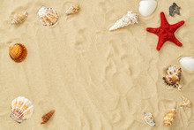 Different Seashells Frame On Beach Sand. Summer Concept With Seashells And Starfish On Beach Sandy Background. Design For Your Summer Decoration With Copy Space. Top View