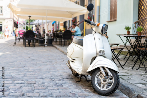 Foto auf Leinwand Scooter Closeup of white scooter parked by European cafe with bokeh background of outdoor restaurant in summer in Lviv or Lvov, Ukraine city