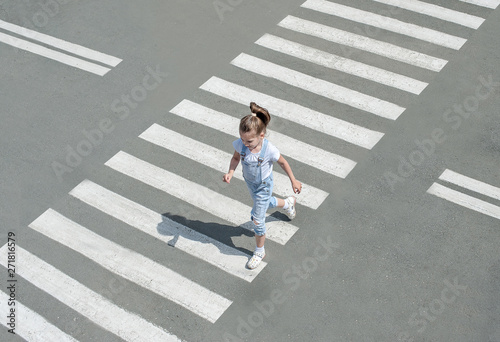 In the summer on the street at the pedestrian crossing kid girl in fashion clothes cross the road Fototapete