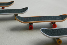 Black Skateboards On Gray Striped Surface. Skate Board Group Of Four With Shadows And Partly Soft Focus. Perspective View Of Extreme Sport Equipment. Red And Yellow Weels