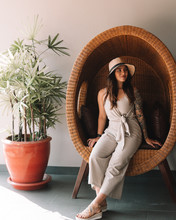 Woman Wearing White Overalls Sitting On Brown Wicker Chair