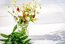 Medicinal Herbs: Branches Of Red Ripe Strawberries, White Daisies And Mint Leaves Stand In A Glass Of Water On A Wooden Stump