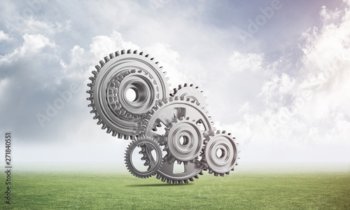 Fototapety, obrazy: Abstract mechanism with cogwheels on green meadow
