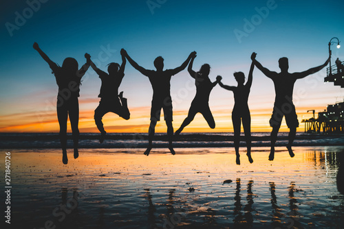 Fotografie, Tablou  Silhouette of jumping friends enjoying summer vacations and youth lifestyle during scenery sunset, group of people holding hands and feeling happiness about friendship