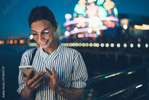 Smiling hipster girl viewing photos in blog enjoying evening leisure in amusement park, cheerful female tourist reading new message on cellphone standing on shiny ferris wheel night background. - 271842729