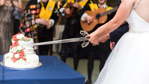 Fotografía  Close-up hands of bride and groom cutting wedding cake with a sword