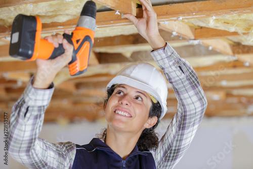 Obraz female builder using cordless drill overhead - fototapety do salonu