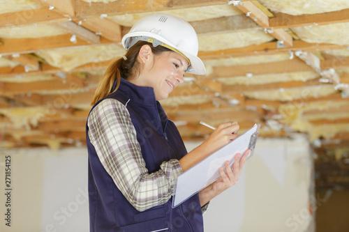 Valokuva  female builder making notes on clipboard at property under renovation