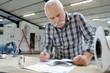 canvas print picture - pleasant senior man working with blueprint