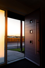 Vertical Shot Of A Wide Open Modern Front Foor Showing Fields And A Sunset In The Distance