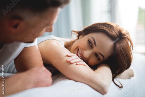 Cute woman smiling to man while lying next to him Tablou Canvas