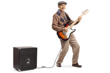 Cheerful Senior Man Playing An Electric Guitar Plugged Into An Amplifier