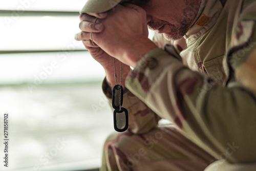 In de dag Eigen foto Low angle of American soldier in camouflage praying indoors