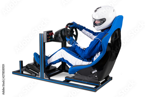 fototapeta na drzwi i meble race driver in blue overall with helmet training on simracing aluminum simulator rig for video game racing. Motorsport car bucket seat steering wheel pedals and isolated white background