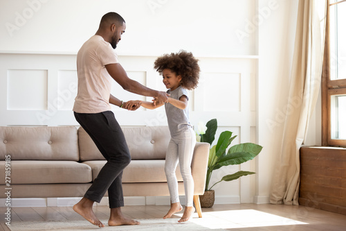 Happy african father and kid daughter jump dance at home - 271859185