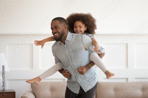 Happy african dad piggybacking little daughter having fun at home Wallpaper Mural
