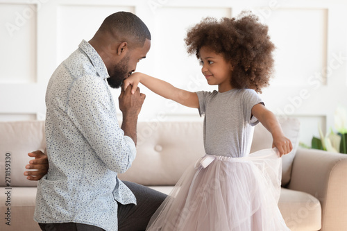 African dad standing on knee kissing hand of kid daughter Tableau sur Toile