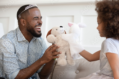 Funny african father wearing crown holding toy playing with daughter