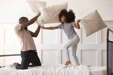 Cute Daughter Playing Pillow Fight On Bed With African Dad