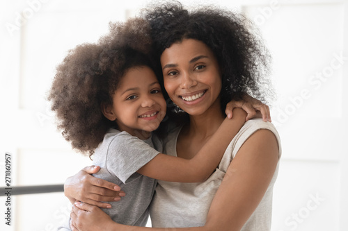 Fotografia African single mother and child daughter embrace looking at camera