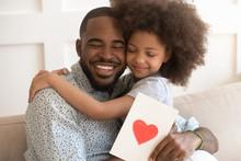 African Dad Embracing Daughter...