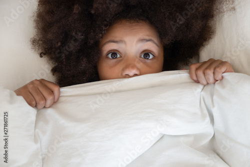 Fotografie, Obraz  Scared african kid looking at camera covering blanket in bed