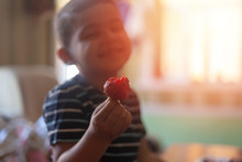 A Little Boy Eating Strawberri...