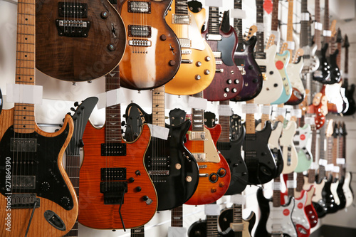 Fond de hotte en verre imprimé Magasin de musique Rows of different guitars in music store