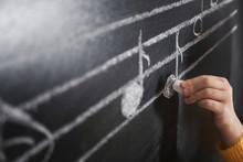 Child Writing Music Notes On B...