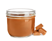 Jar Of Tasty Caramel Sauce And Candies Isolated On White