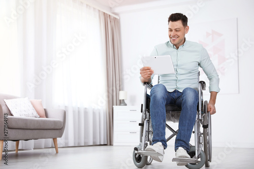 Fotografie, Obraz  Happy man with tablet sitting in wheelchair at home
