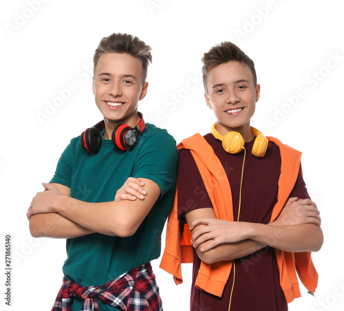 Photo  Teenage twin brothers with headphones on white background