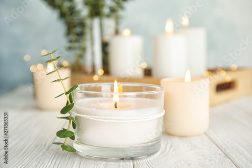Fotografie, Tablou Burning aromatic candle and eucalyptus branch on table