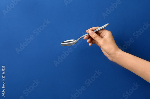 Fotografia, Obraz  Woman holding empty table spoon on color background, closeup