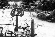 A Rusting Antique Plow Sits In A Snowy Field. Black And White Image, Copy Space, Background