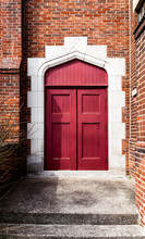 Exterior Rich Red Arched Doorway In A Brick Wall, Framed In Stone. No Handles On Doors.