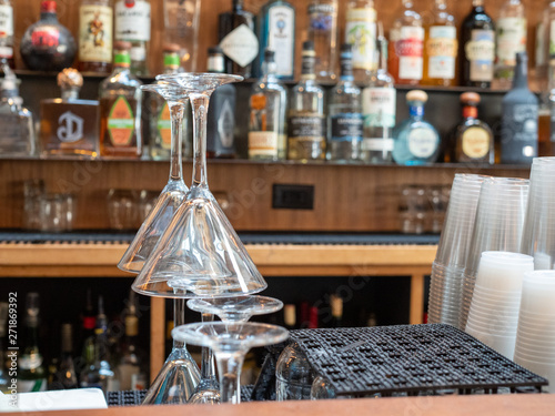 Valokuva  Martini glasses stacked behind a busy bar with plastic cups and liquor