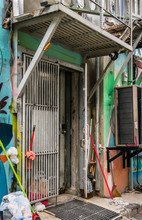 Open Alleyway Iron Gated Security Door At Rear Of A Business Location, Below Fire Escape, With Cleaning Supplies, Graffiti And Security Camera
