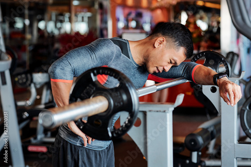 fototapeta na drzwi i meble Tired young Vietnamese man standing at workout bench and leaning on barbell after doing exercise